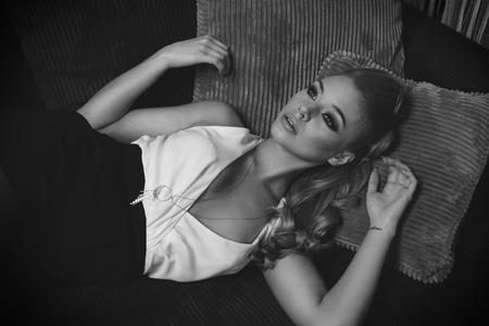 modelos posando: blanco y negro la imagen de una mujer joven rubia muy linda y dulce, que pone en el sofá, ella tiene vestido elegante, y el pelo largo. ella está mirando hacia arriba con una expresión soñando Foto de archivo