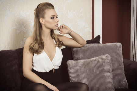 fashion model: elegant fashion woman with cute make-up and long blonde hair sitting on comfortable sofa. Freckles on visage
