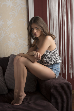nude girl sitting: very pretty young girl with long brown hair is sitting on sofa with denim shorts and looking in camera.