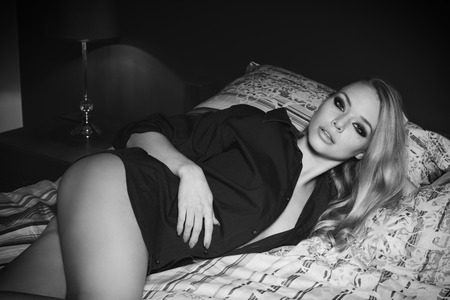 nude blonde girl: black and white ,beautiful blonde girl posing lying on bed with nude legs, unbuttoned blue shirt and fashion make-up. She is looking in camera with charming and relaxed expression , Stock Photo