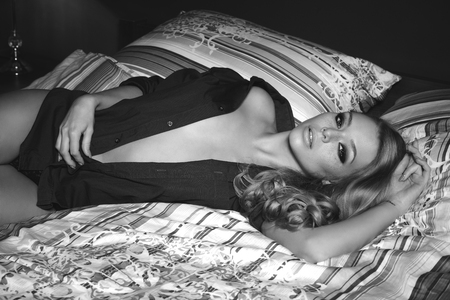 model home: sensual blonde woman with freckles lying on bed with unbuttoned blue shirt and stylish make-up. She is looking in camera in black and white shot
