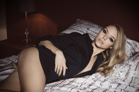 nude blonde girl: beautiful blonde girl posing lying on bed with nude legs, unbuttoned blue shirt and fashion make-up. She is looking in camera with charming and relaxed expression