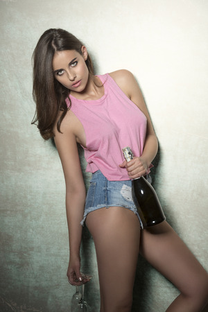 party outfit: stunning brunette woman with fit body, shorts and pink top ready for party taking a bottle of champagne and two glasses in the hands. She is looking in camera with charming expression