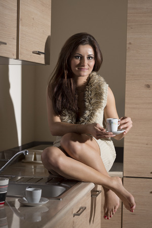sensual brunette woman with happy expression is sitting in kitchen with sexy short wool dress and a cup of coffee in the hand Stock Photo
