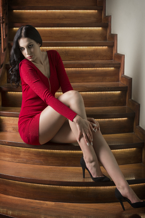 heel: cute woman with long black hair, sexy short red dress and heels, sitting on elegant wood stairs in fashion pose