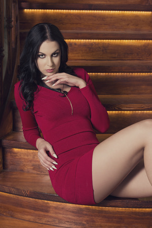 beautiful girl with long brown hair, short red dress, sexy legs in sexy fashion pose is sitting on wood stairs