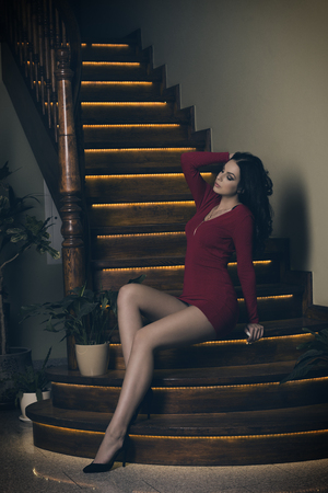 brunette woman with long black hair and sexy red dress in fashion pose sitting on elegant wood stairs Standard-Bild
