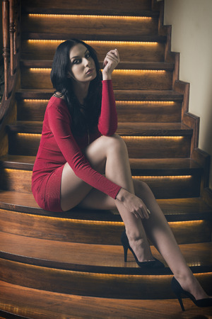 stunning female with long black hair wearing short red dress and heels and sitting on elegant wood stairs in fashion pose Stock Photo