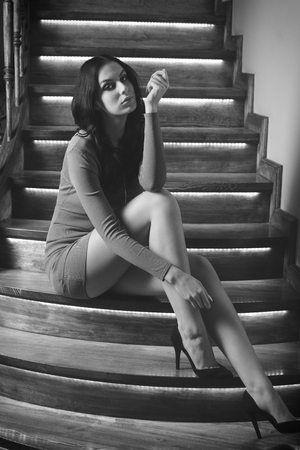 tacones rojos: impresionante mujer con pelo largo y negro con un vestido corto de color rojo y zapatos de tacón y elegante que se sienta en las escaleras de madera en actitud de la manera. blanco y negro convertido.