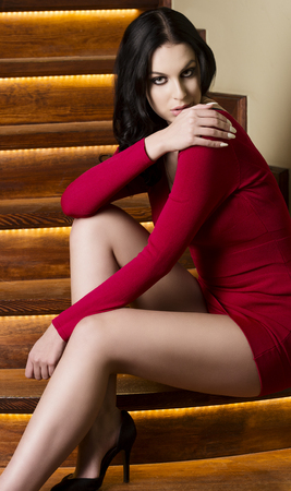 fashion portrait of beautiful girl with long black hair, short red dress, sexy legs and heels is sitting on wood stairs and looking in camera with flirty expression