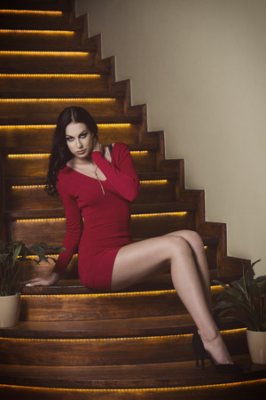 party outfit: fashion portrait of beautiful woman with long brown hair, short red dress, sexy legs and heels is sitting on wood stairs in sensual pose near some plants Stock Photo