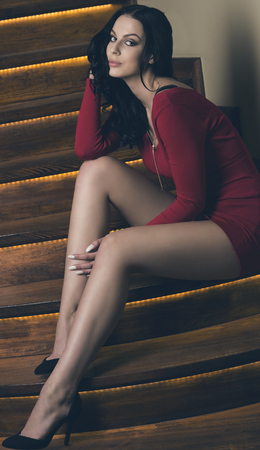 sensual woman with long black hair, sexy red dress and cute legs is sitting on elegant stairs and looking in camera