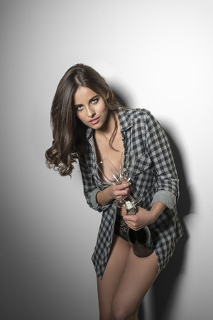 lace panties: sexy brunette woman with unbuttoned plaid shirt, lace panties and nude legs taking a bottle of champagne in the hand and two glasses. Ready for sexy party. Stock Photo