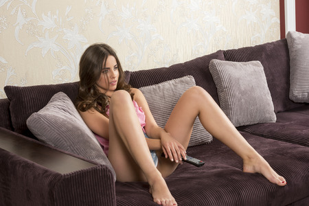 provocative women: sexy woman is looking television on comfortable sofa with shorts. She is taking remote control in the hands Stock Photo