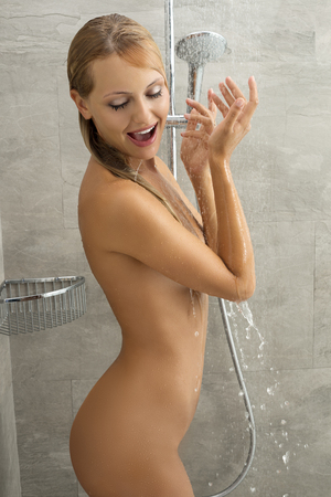 sexy naked blonde woman under shower with funny expression. Perfect body photo