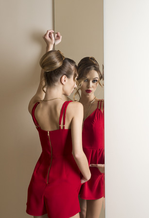 changing room: woman with make-up and hair-style trying elegant red dress in changing room in front of mirror