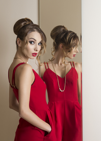 changing room: fashion woman with hairdo and make-up trying red dress in front or the mirror. Changing room. Shopping time
