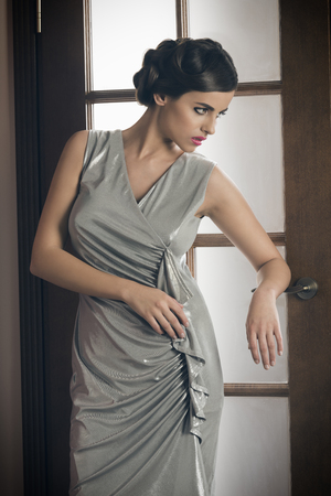young woman nude: elegant fashion woman posing near door with silver dress, make-up and hair-style