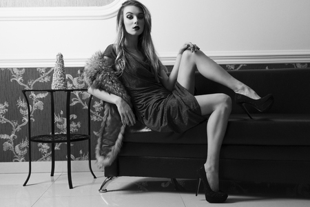 stunning woman is sitting in sexy pose on leather sofa in elegant ambient with evening blue dress, heels and fur on shoulder. She is looking in camera and showing her sensual legs .BW shot