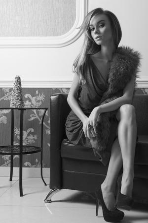 traje de gala: elegante femenino mirada rica de moda está sentado en el sofá de cuero con el vestido de noche azul, piel sobre los hombros y los talones. El pelo largo y el maquillaje. imágenes en blanco y negro Foto de archivo