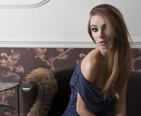 blue leather sofa: sensual elegant woman with blue dress is sitting on leather sofa near fur. sensual fashion woman with make-up, she is looking in camera with lovely expression Stock Photo