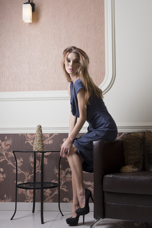 blue leather sofa: sensual girl with shiny blue dress and heels posing in elegant ambient with fur on leather sofa