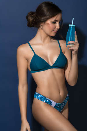 girl in summer swimsuit looking at her drinking bottle , everything on blue