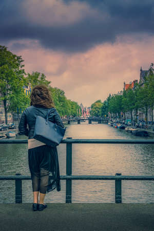 Young women with bag and skirt and long hairs standing on a bridge and looking at Amsterdam canal from behind. Back view with dramatic cloudy sky.