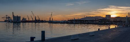 Sunset on the Port of Malaga Spain wide panorama. Docks with cranes silhouette with the sun setting behind the hills in backlight. Archivio Fotografico