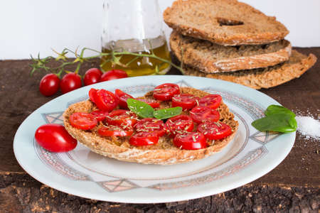 dried food: Freselle with tomatoes photographed on a wooden base