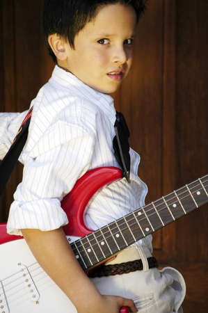 Boy looking backward with a red guitar Stock Photo