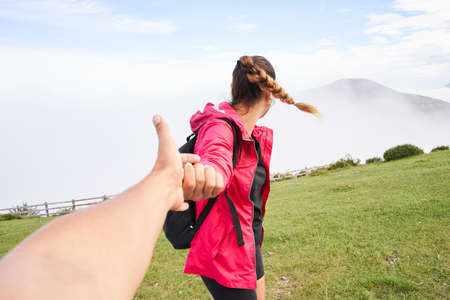 POV of man following his girlfriend in the mountains. Happy couple traveling. She wears a red jacket and walks along a green meadow. In the background you can see a mountain surrounded by fog.