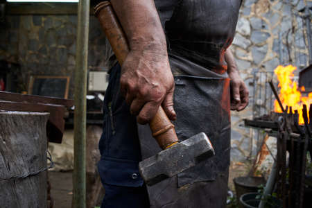 Close up of a blacksmith's hand holding a hammer.The owner and worker of a small smithy who works in his trade. The hand is dirty because it has been working.