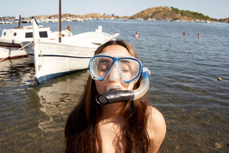 Funny little girl on the beach in a diving mask making a silly face. Closed portrait of a girl on her travel vacation. Summer or winter destination.