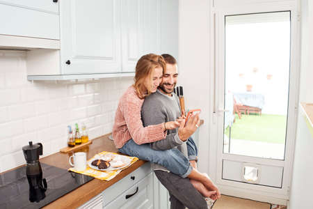 Happy young couple in kitchen at home, using mobile phone Reklamní fotografie
