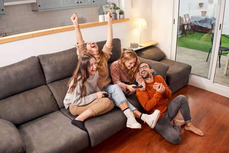 Group of friends sitting on sofa in living room and playing video games at home.
