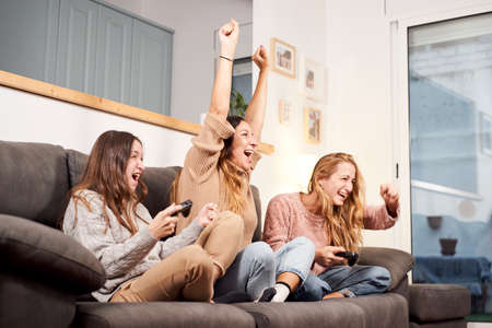 Group of female friends sitting on sofa in living room and playing video games at home.
