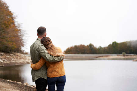 Back view of lovely young couple hugging at the lake. Copy space.