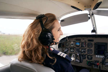 Smiling female pilot in the cockpit of an airplane.