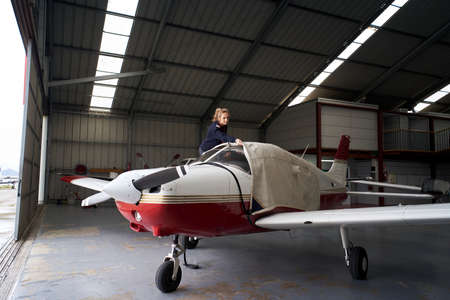 Young female pilot covering light aircraft with protective cover in hangar.