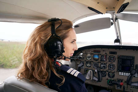 Woman Pilot Sitting in Cabin of plane.