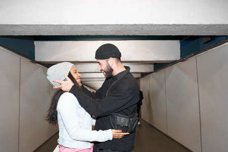 Young interracial couple of lovers wearing face masks in an underground subway corridor in each other's arms down an old public transportation corridor looking at each other and enjoying their love.