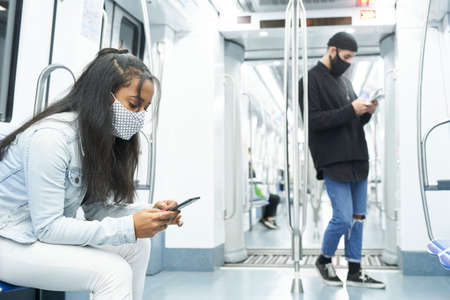 Young people in public transport abducted by technology. An African American girl and a Caucasian boy using the smartphone in the subway car.