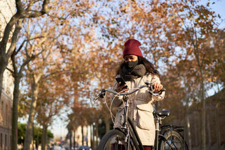 Young African-American woman on her bicycle using her smartphone. She is wearing winter clothes, and is in a city with autumn weather.