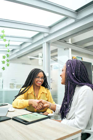 Vertical shot of happy and satisfied businesswomen shaking hands after successful negotiations, black African businesswoman shaking hands with a new business partner closing a good deal.