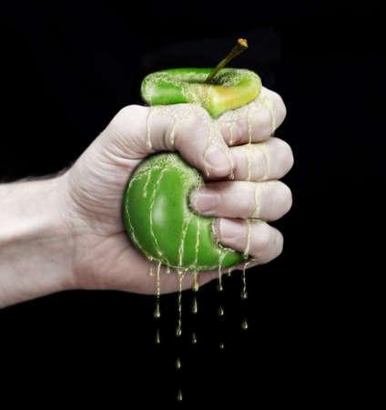 squeezed: mano para exprimir una manzana verde aislada en fondo negro