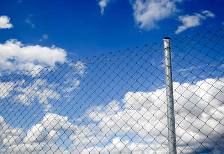 Suggestive image of metal fence against the sky photo
