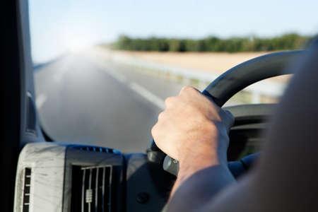 man driving: Detalle de la mano del conductor y la carretera