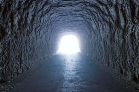 light tunnel: Inside a tunnel inside a mountain with light at the end Stock Photo