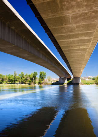 Close up image of under a bridge with a river photo